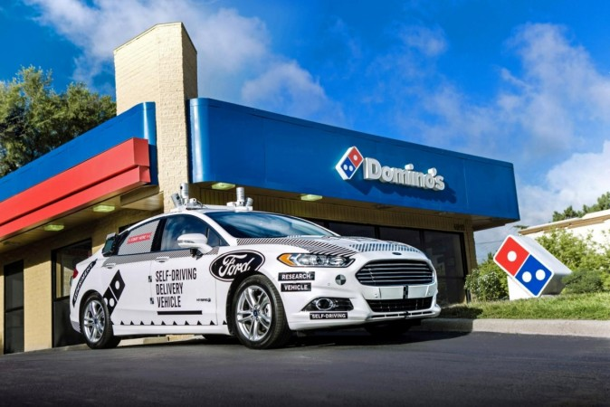 A Ford self-driving delivery vehicle is pictured in front of a Domino's pizza restaurant