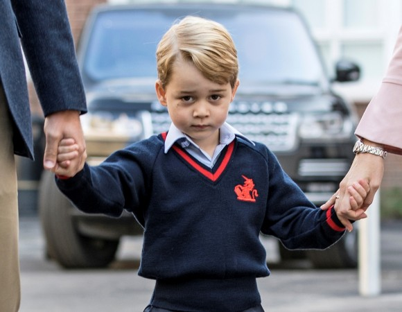 Prince George holds his father Britain's Prince William's hand as he arrives on his first day of school at Thomas's school in Battersea, London.
