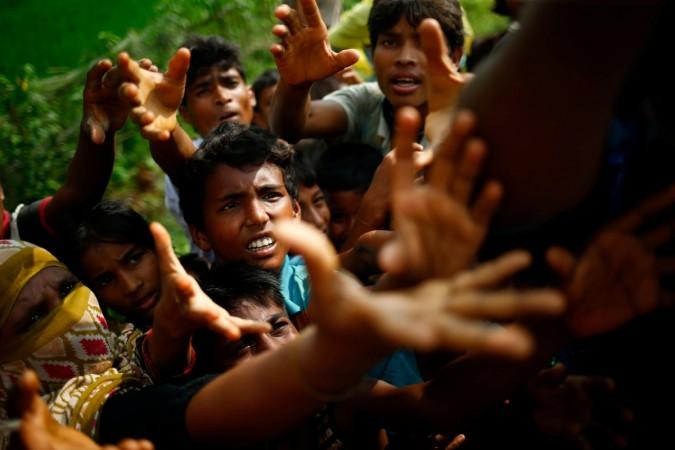 Rohingya refugees stretch their hands for food near Balukhali in Cox's Bazar, Bangladesh.