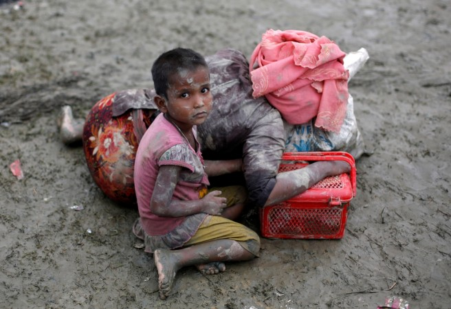 A Rohingya refugee girl sits next to her mother who rests after crossing the Bangladesh-Myanmar border, in Teknaf, Bangladesh.
