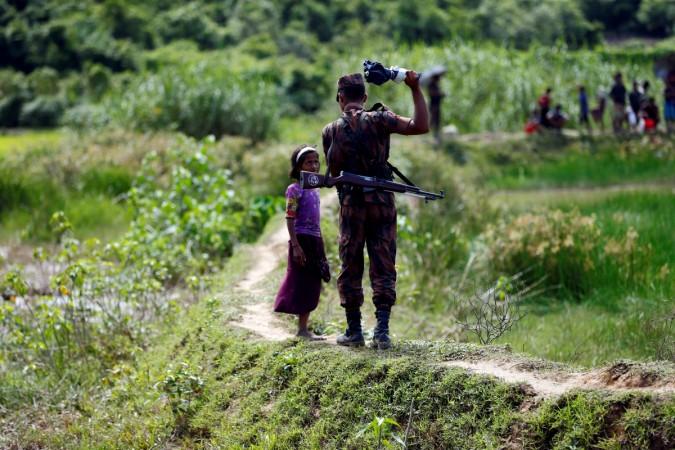 A member of Border Guard Bangladesh (BGB) tells a Rohingya girl not to come on Bangladesh side, in Cox's Bazar, Bangladesh