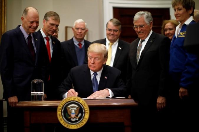 Donald Trump firmando la directiva que faculta a la NASA a preparar el camino de vuelta a la Luna con el objetivo final de conquistar el planeta Marte.
