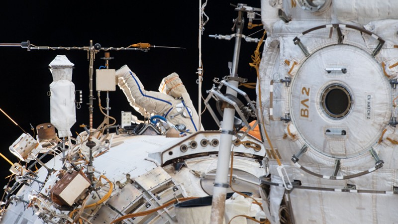 A Russian spacewalker is seen in an Orlan spacesuit with blue stripes (center image) working outside the Zvezda service module during the longest spacewalk in Russian space program history on Feb. 2, 2018.