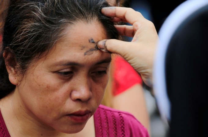 A Catholic nun marks a cross on the forehead of a devotee using ash during the observance of Ash Wednesday