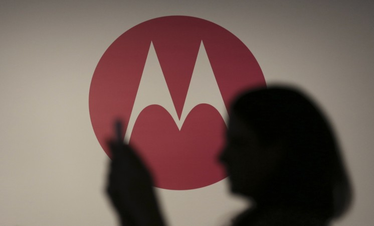 A woman takes a picture in front of a Motorola logo before the worldwide presentation of the Moto G mobile phone in Sao Paulo November 13, 2013.