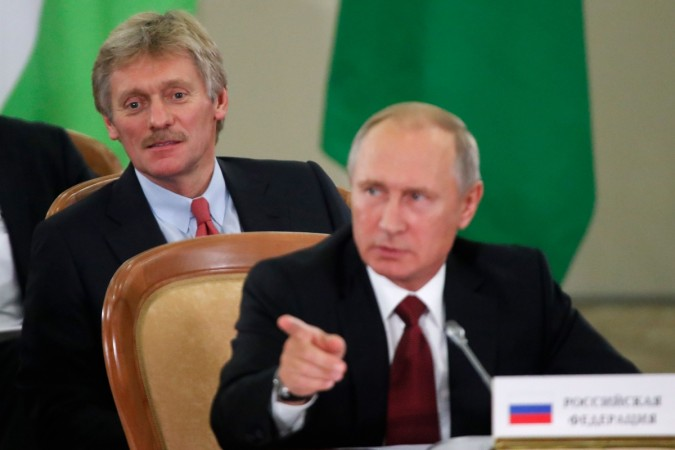 Russia's President Vladimir Putin (front) and Kremlin spokesman Dmitry Peskov attend a session of the Council of Heads of the Commonwealth of Independent States (CIS) in Sochi on October 11, 2017.