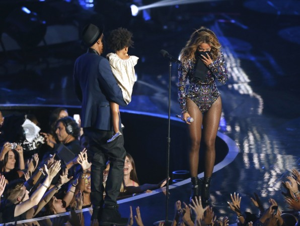 Beyonce reacts as her husband Jay-Z carries their daughter Blue Ivy onstage to present the Video Vanguard Award during the 2014 MTV Video Music Awards in Inglewood, California August 24, 2014.