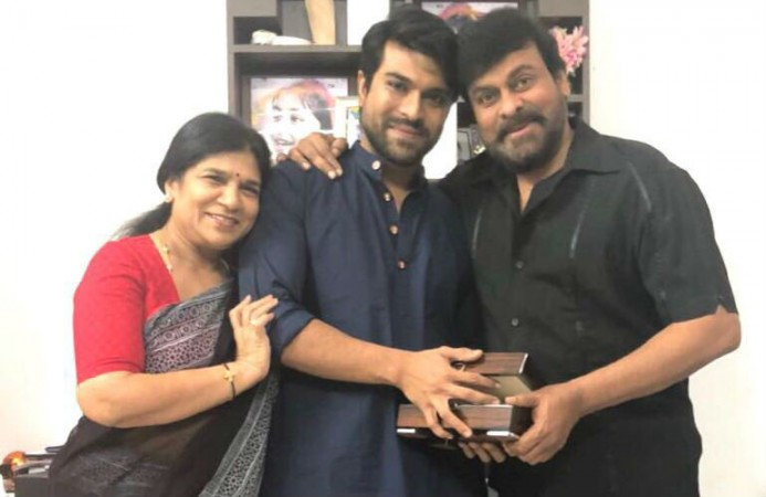 Chiranjeevi and his wife Sureka presenting special gift to son Ram Charan