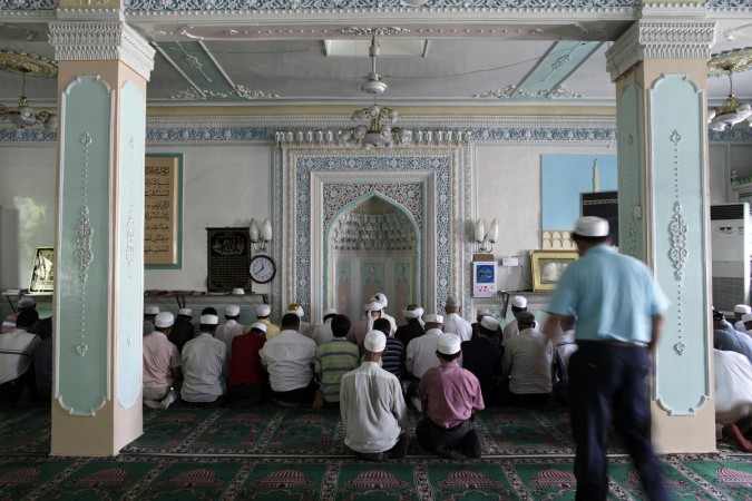 Ethnic Uyghurs pray inside a mosque