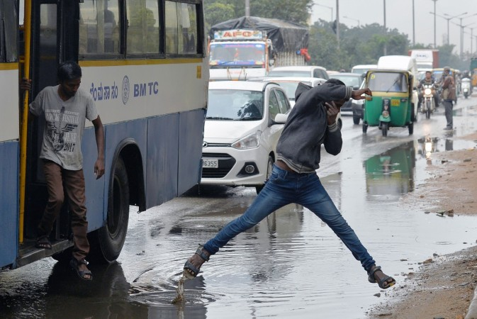 An Indian pedestrian jumps a puddle of water as he crosses the road after copious rains in Bangalore