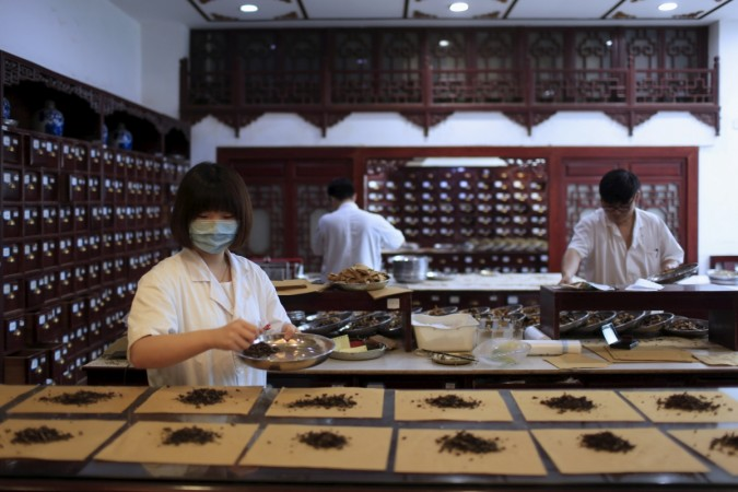 Employees work at a traditional Chinese medicine shop in Shanghai, China,