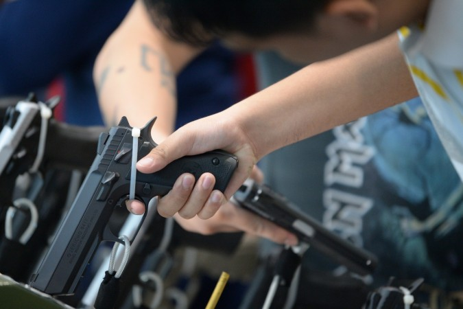 Visitors examine handguns for sale during the opening of the annual gun show in Manila