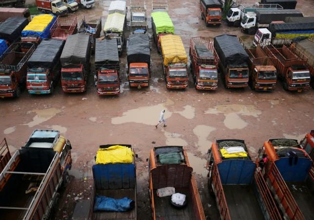 driver walks past parked trucks