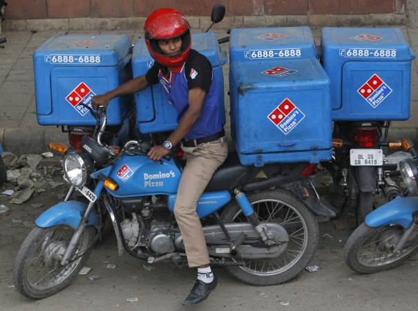 An employee rides a motorcycle to deliver Domino's Pizza
