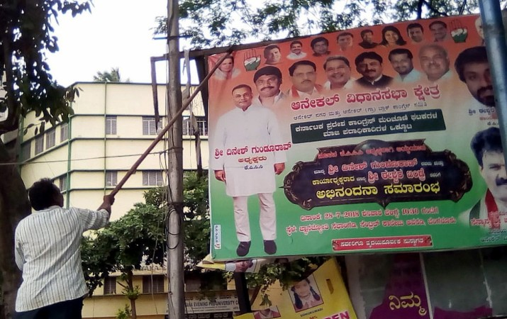 An illegal hoarding promoting the Congress party being torn down by the BBMP