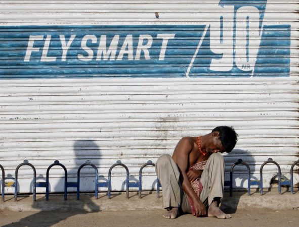 An unemployed migrant worker sits on a pavement in Mumbai