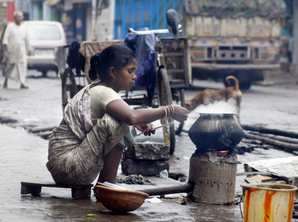 Unemployed Rupa Kaha prepares her lunch beside a busy street in Calcutta.