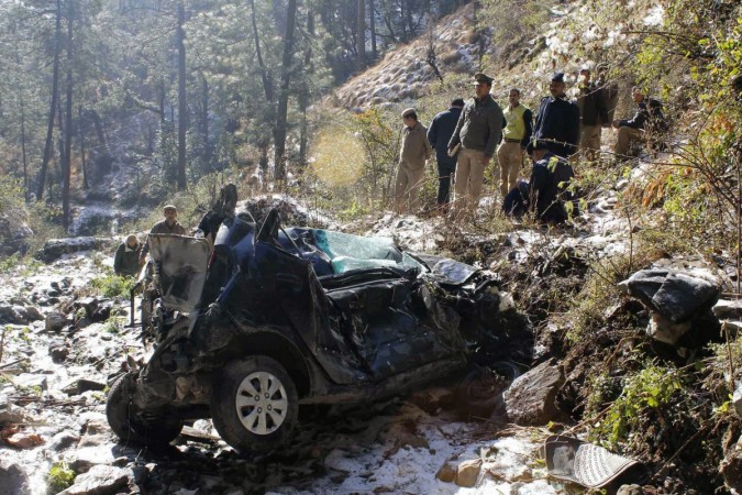 Police are seen gathered near the wreckage of a car which fell into a gorge at Tutikandi near Shimla