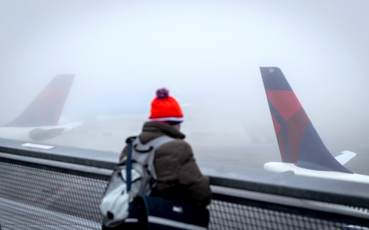 A person watches planes on the tarmac at the Schiphol Airport, The Netherlands, on December 28, 2016