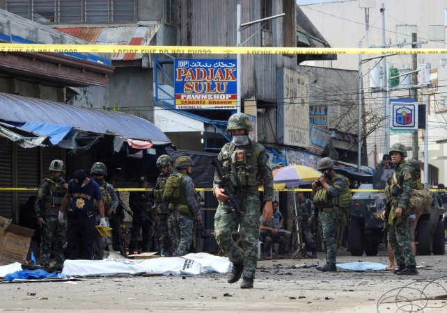 Policemen and soldiers keep watch as body bags (in white), containing the remains of blast victims, as seen in a cordoned area outside a church in Jolo