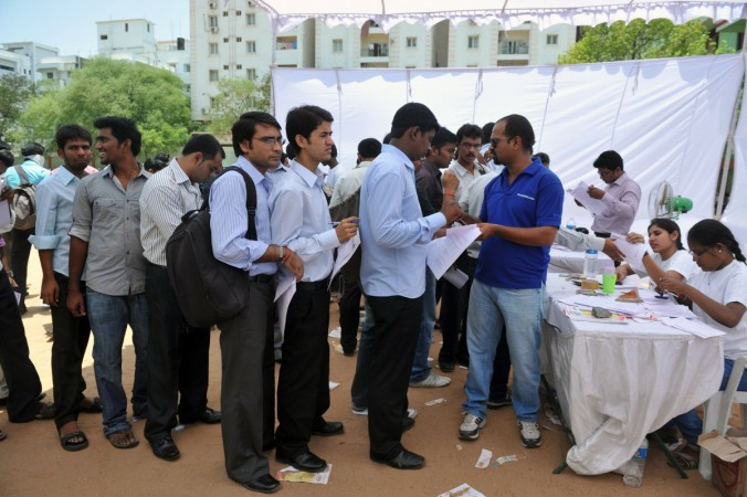 Job-seekers wait in line to register at a career fair held at a school in Hyderabad on May 19, 2012