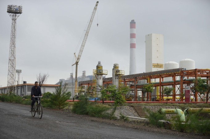 a worker cycling by an Indian oil refinery