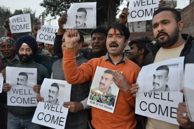 Indian people hold placards and photographs of Indian Air Force pilot Abhinandan Varthaman, as they celebrate the announcement of his soon release, in Amritsar on February 28, 2019