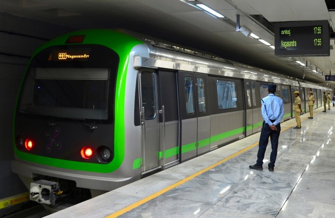 Security personnel watch the trial run of a train running on the yet to be inaugurated Green Line of the Namma Metro Rail at Majestic Station