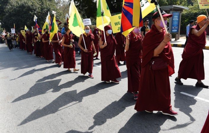 Tibetan exile activists and monks hold Tibetan flags