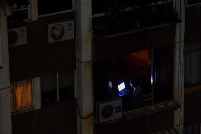 A man uses a laptop during a power outage in Caracas, Venezuela, on March 26, 2019