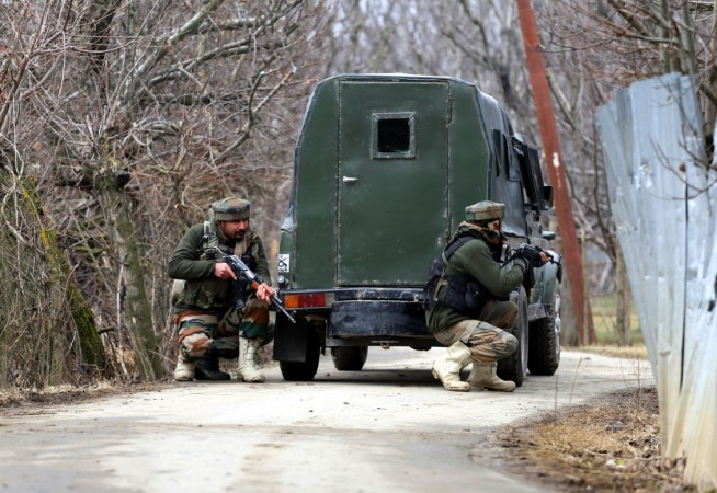 Soldiers take position during a gun-battle with militants at Rehmatabad village in Jammu and Kashmir's Sopore district on Feb 21, 2015.