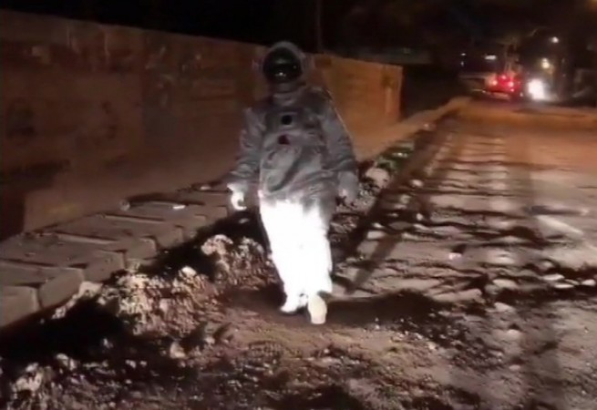 Baadal Nanjundaswamy, an artist dressed up as an astronaut in a Bengaluru road to highlight the pothole issues in the city