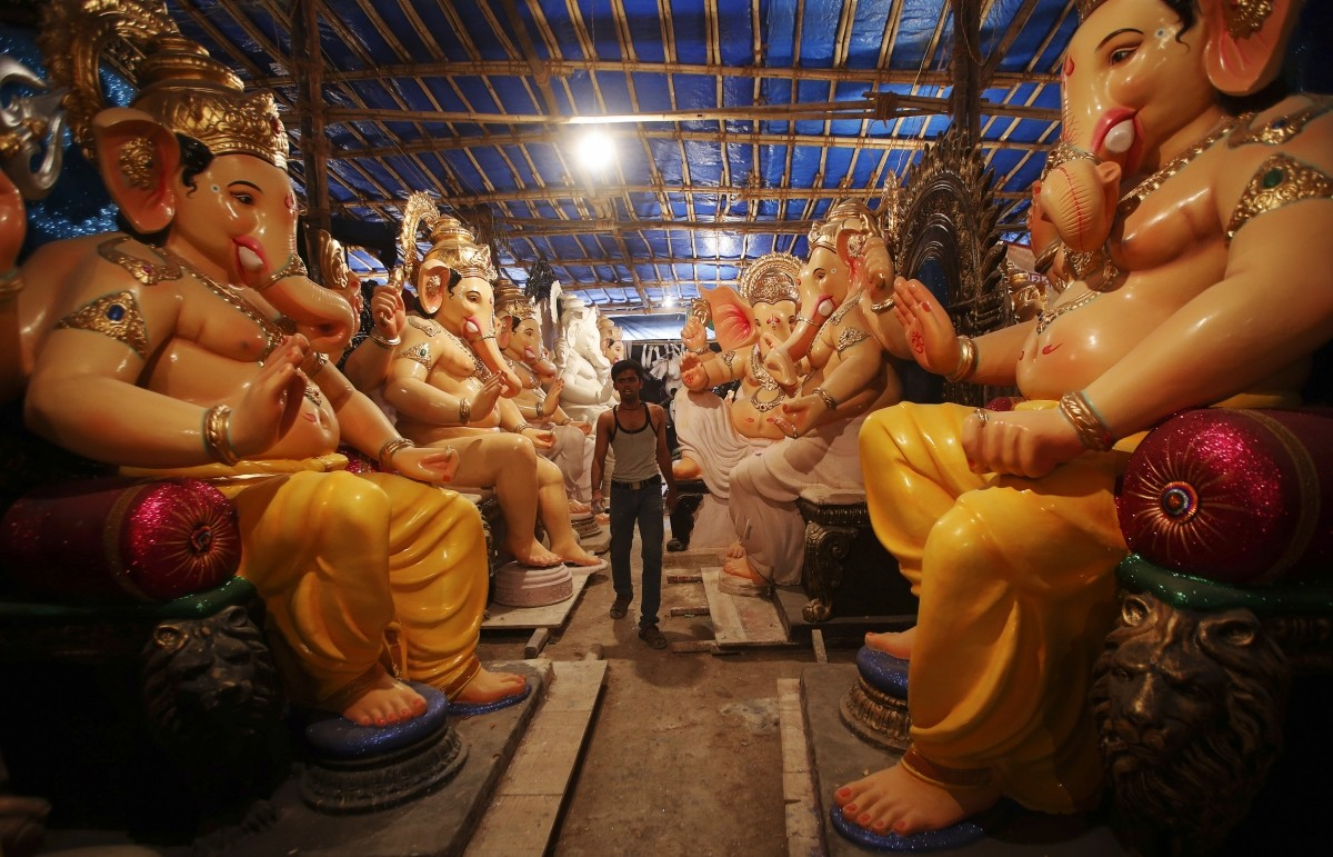 An artisan walks amidst idols of Ganesh