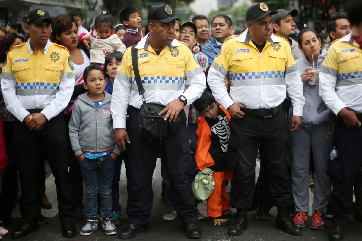 A boy holds a mask between traffic policemen in a Zombie Walk procession in Mexico City, Mexico, October 22, 2016..
