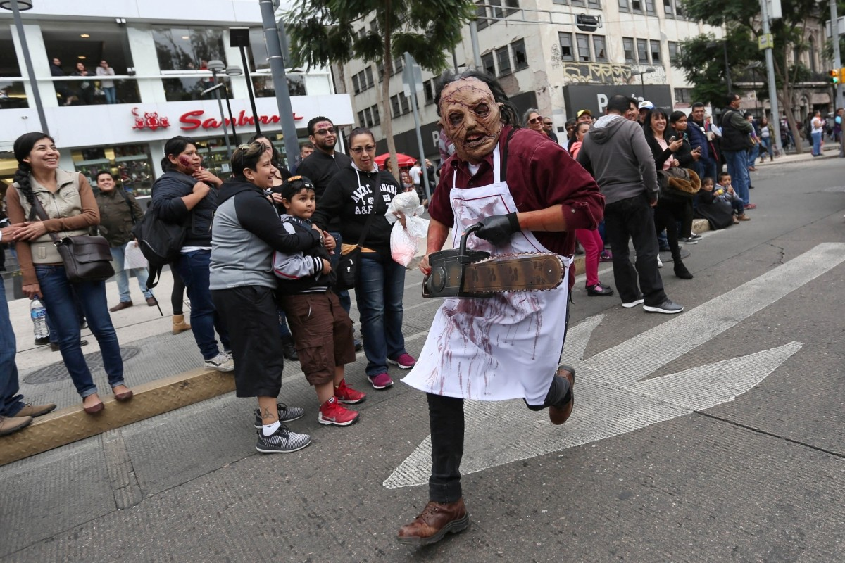 A man dressed as zombie runs as he participates in a Zombie Walk procession in Mexico City, Mexico, October 22, 2016.