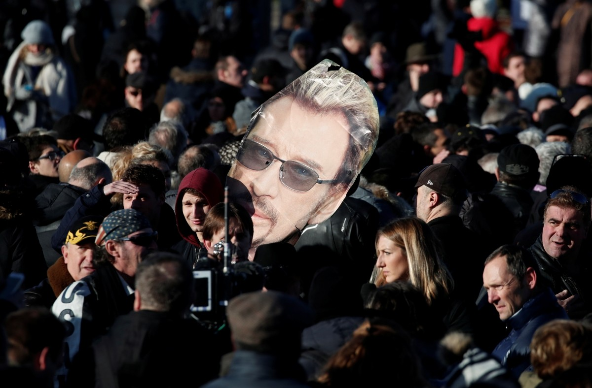 Fans gather on the Champs Elysees avenue during a 'popular tribute' to late French singer and actor Johnny Hallyday in Paris, France, December 9, 2017.