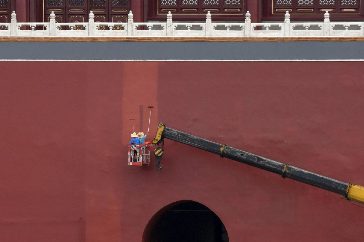Workers paint a red wall of the Forbidden City in central Beijing