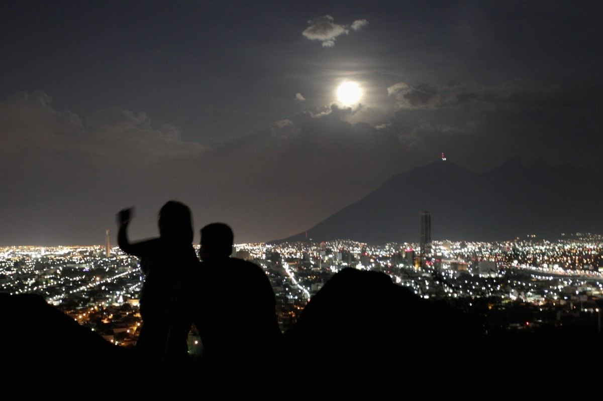 A supermoon rises while a couple takes a photo in Monterrey August 10, 2014.