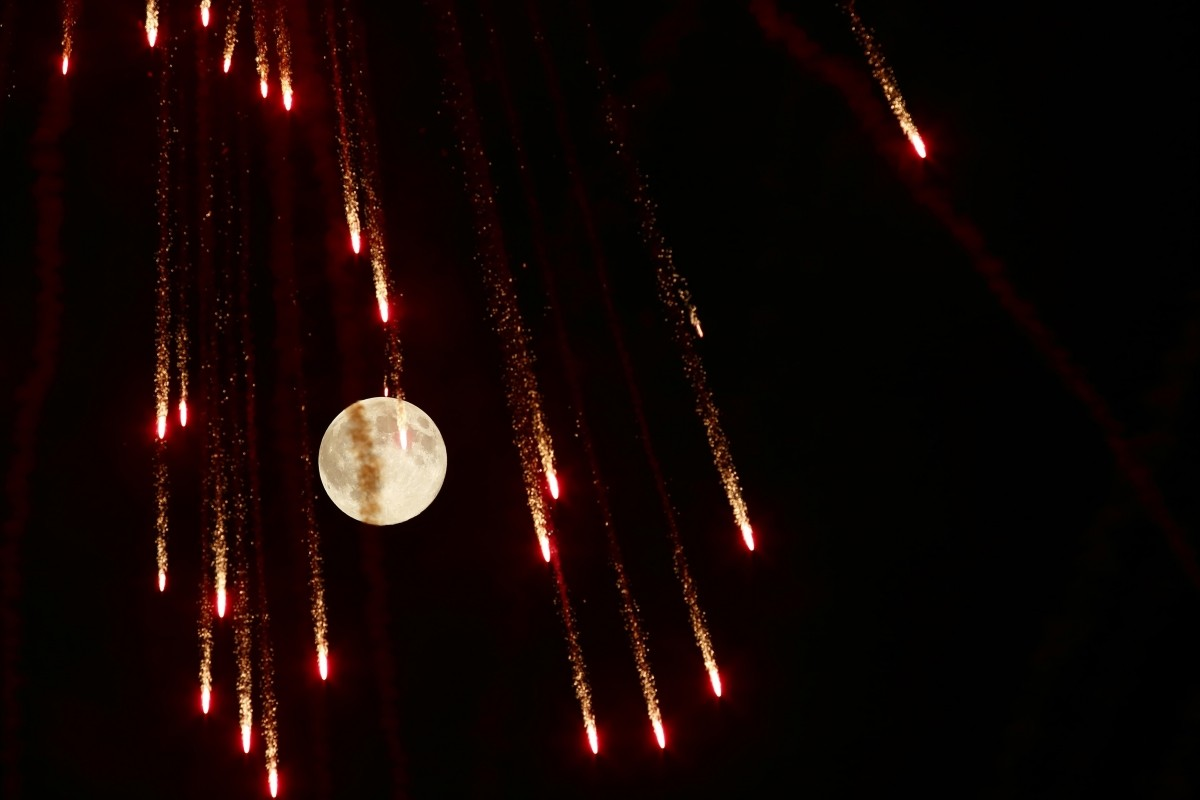 Fireworks streak past in front of the supermoon outside the town of Mosta, celebrating the feast of its patron saint, in central Malta, August 10, 2014.