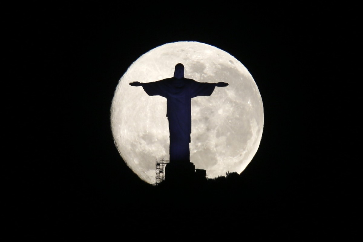 The supermoon is pictured behind the Christ the Redeemer statue in Rio de Janeiro August 11, 2014.