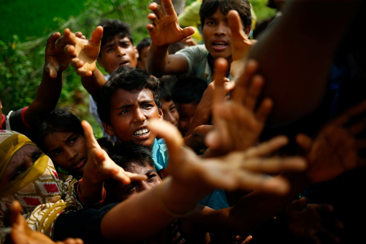 Rohingya refugees stretch their hands for food near Balukhali in Cox's Bazar, Bangladesh.