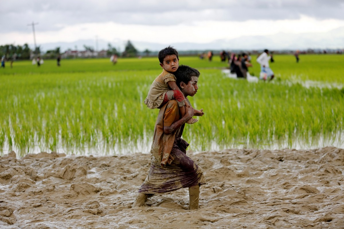 A Rohingya boy carries a child while walking in the mud after crossing the Bangladesh-Myanmar border in Teknaf, Bangladesh