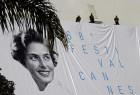 Workers set up a giant canvas of the official poster of the 68th Cannes Film Festival, featuring late actress Ingrid Bergman, on the Festival Palace in Cannes