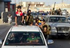 Tribal fighters and Iraqi security forces take part in a parade down a street in the city of Ramadi