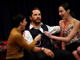 People pose next to Madame Tussauds' wax figure of British actor Tom Hardy which has a soft warm chest and a beating heart, in London, Britain.