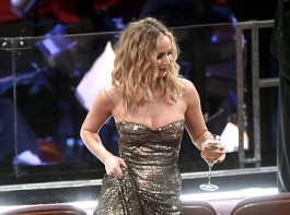 Actress Jennifer Lawrence was seen hitching up her sequinned dress to climb over rows of chairs to get to her seat at the 90th Academy Awards here -- and that too with a wine glass in hand.
