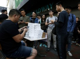 A man pays to buy new iPhone Xs from those who just bought at Apple Stores, on a street in Hong Kong, China November 3, 2017.