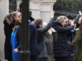 Embassy staff wave as colleagues and children board buses outside Russia's Embassy in London.