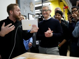 Tim Cook, Chief Executive Officer of Apple Inc., looks at a iPad, as he tours a technology lab, at an education-focused event at Lane Technical College Prep High School in Chicago, Illinois, U.S.