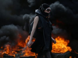 A protester walks near burning debris that barricades a road as French gendarmes continue an evacuation operation in the zoned ZAD (Deferred Development Zone) at Notre-Dame-des-Landes, near Nantes, France, April 12, 2018.